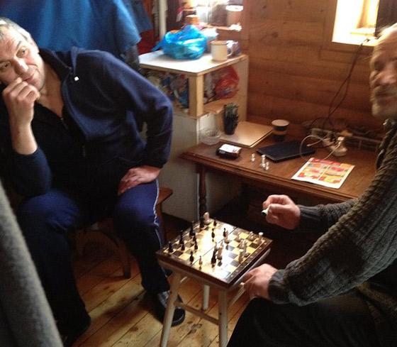 Двое мужчин, у которых сегодня выходной, проводятсвой досугза шахматной доской