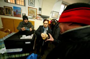 Волонтер раздает пищу бездомным близ Ватикана. Фото с сайта star2.com